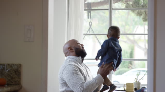 stockvideo's en b-roll-footage met single dad reading a book, playing, and feeding his 2 years old son - genderblend