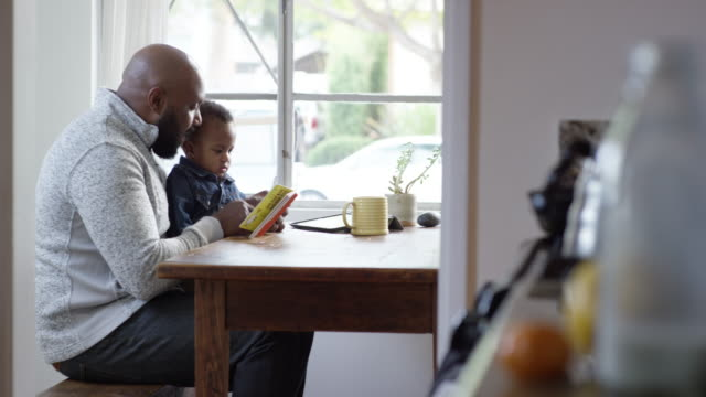 Single dad reading a book, playing, and feeding his 2 years old son