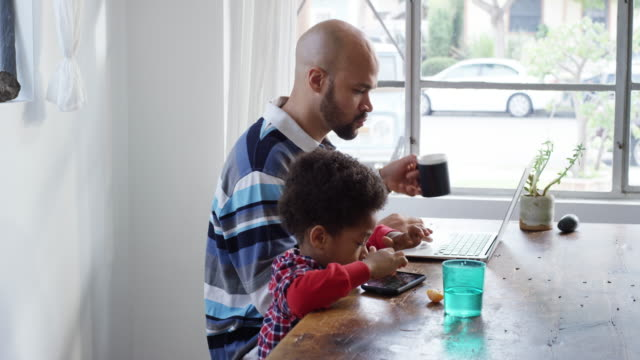 Single dad working on computer with his son playing on smartphone and eating