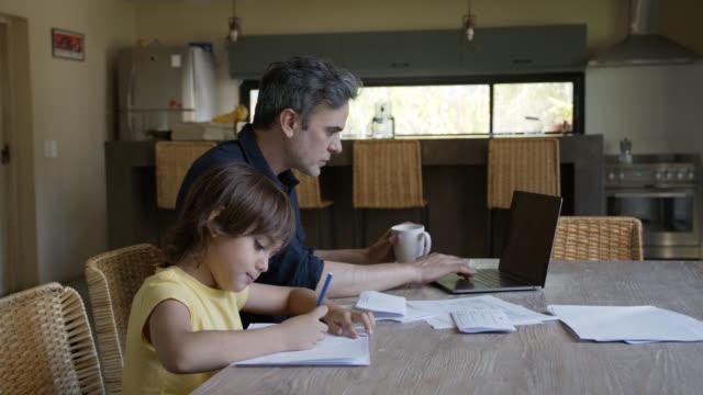 vídeos de stock e filmes b-roll de single daddy working on laptop while son is sitting next to him doing homework - teletrabalho
