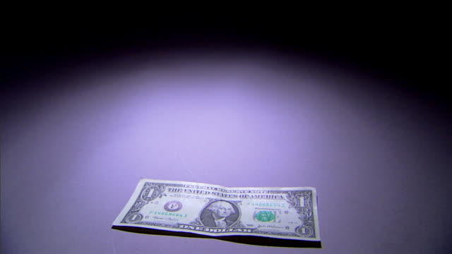 A single dollar bill falls to a spotlighted surface.