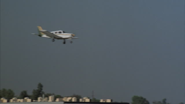 A single engine airplane approaches a rural airport for landing.
