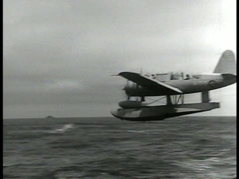 vidéos et rushes de single engine fighter seaplane launching from aircraft carrier at sea ms antiaircraft crewmen manning guns on deck looking up wwii - 1942