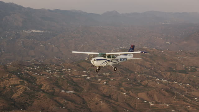 MS single engine training aircraft flying over arid hilly landscape, air-to-air view, RED R3D 4K