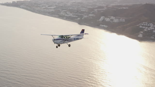 WS single engine training aircraft in banked (turning) flight above coastline and ocean, air-to-air view; camera and airplane turn in sync, RED R3D 4K