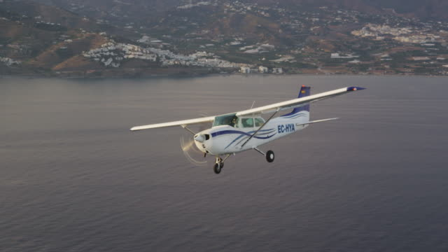 CU single engine training aircraft in flight above coastline and ocean, air-to-air view, RED R3D 4K