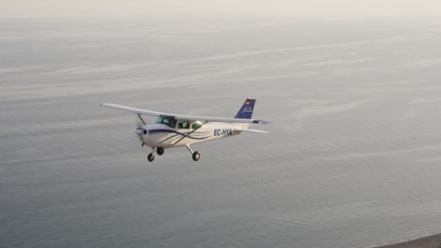 ms single engine training aircraft in  flight above ocean,, air-to-air view, red r3d 4k - horizon over water stock-videos und b-roll-filmmaterial