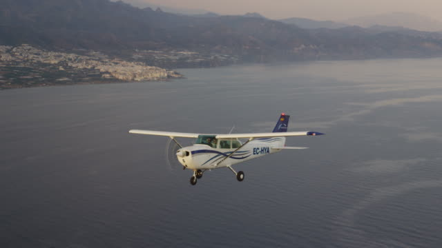 CU single engine training aircraft in flight over mountainous coastline and ocean, air-to-air view, RED R3D 4K
