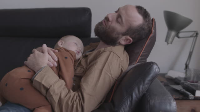 vídeos de stock e filmes b-roll de single father and baby sleeping on sofa in living room - descansar