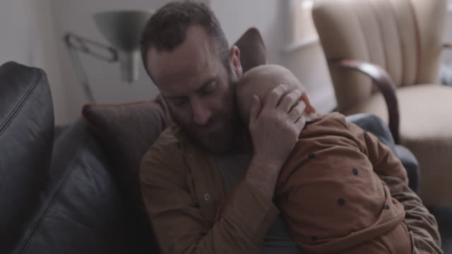 single father and baby sleeping on sofa in living room - genderblend stock videos & royalty-free footage