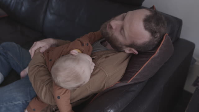single father and baby sleeping on sofa in living room - single father stock-videos und b-roll-filmmaterial