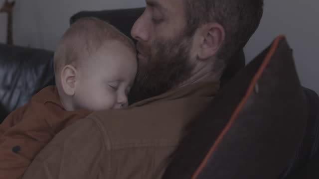 single father and baby sleeping on sofa in living room - hair stubble stock videos & royalty-free footage