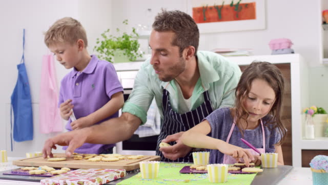 single father and two kids (brother + sister) preparing cookies in kitchen