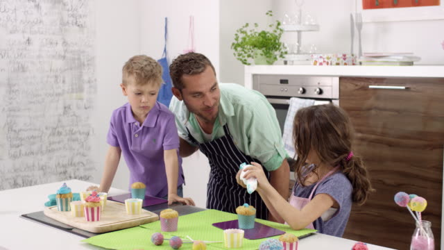single father and two kids (brother + sister) preparing cup cakes in kitchen - cupcake stock videos & royalty-free footage
