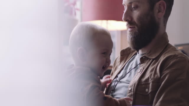 single father comforts crying baby boy sitting on lap - stanco video stock e b–roll