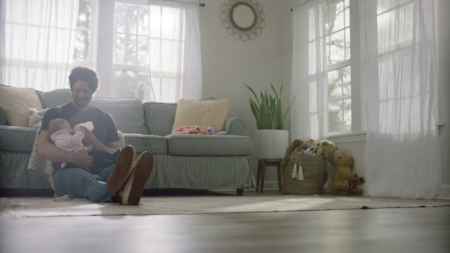 a single father cradles and nurses his daughter with baby bottle as sunlight spills in through the living room windows. - enbarnsfamilj bildbanksvideor och videomaterial från bakom kulisserna