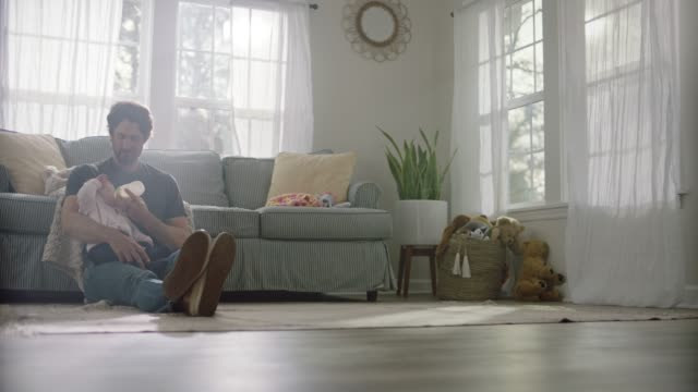 slo mo. a single father cradles and nurses his daughter with milk bottle in sunny home living room. - milk bottle stock videos & royalty-free footage