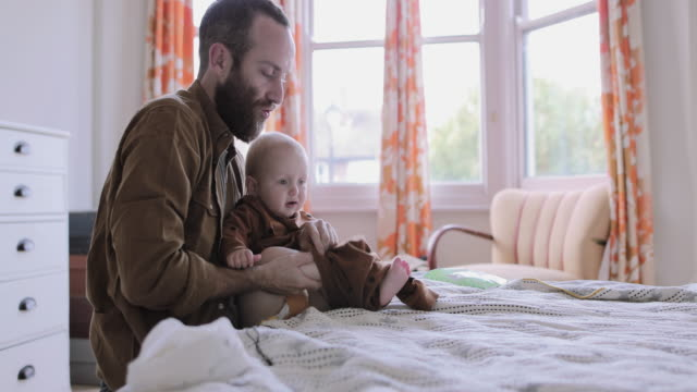 single father dressing baby on bed in bedroom - single father stock-videos und b-roll-filmmaterial