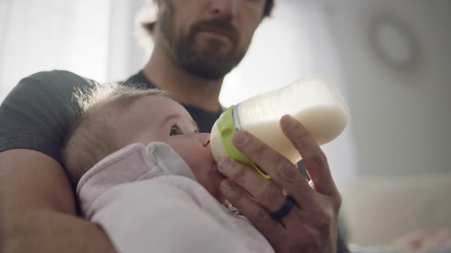 slo mo. a single father feeds his baby milk from a bottle. - geburt stock-videos und b-roll-filmmaterial