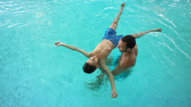 single father in his 30s with his pre-adolescent 8 years old child is floating his son on the water in the turquoise blue water of a thermal indoor swimming pool, this aqua balancing is very healing and digital detoxing - top shot - 30 39 years点の映像素材/bロール