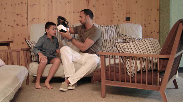 vídeos de stock, filmes e b-roll de single father in stylish hotel lounge - his 8 years old son entering with top notch virtual reality head set - vr glasses and the father helps him with the virtual reality simulator and smart phone - the man in his 30s has short dark hair + trimmed beard. - 30 39 years