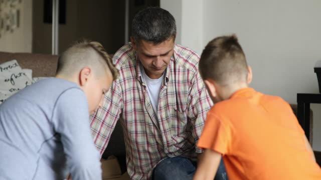 alleinerziehender vater ist mit seinen kindern möbel montage. - single father stock-videos und b-roll-filmmaterial