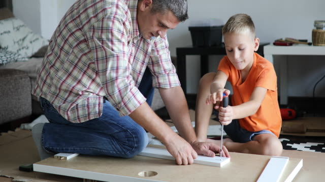 single father is assembling furniture with his kids - work tool stock videos & royalty-free footage