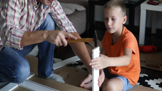 single father is assembling furniture with his kids - pre adolescent child stock videos & royalty-free footage