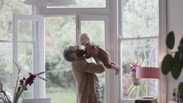 single father lifting baby and playing in living room - single father stock-videos und b-roll-filmmaterial