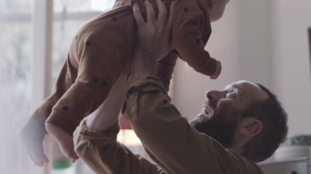 single father lifts baby boy in air playfully - genderblend stock videos & royalty-free footage