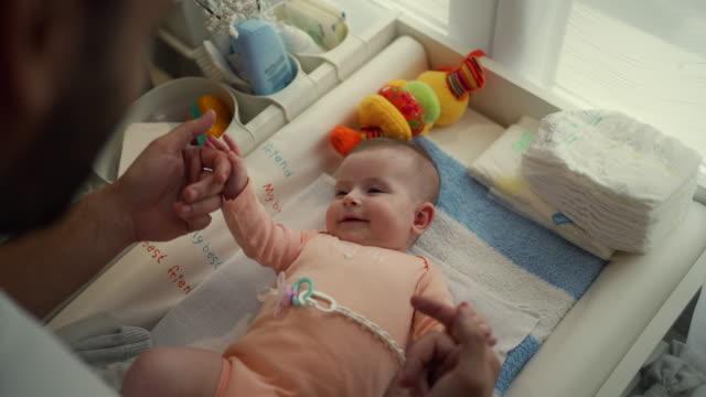 vidéos et rushes de père célibataire jouant avec son petit bébé - chambre de bébé