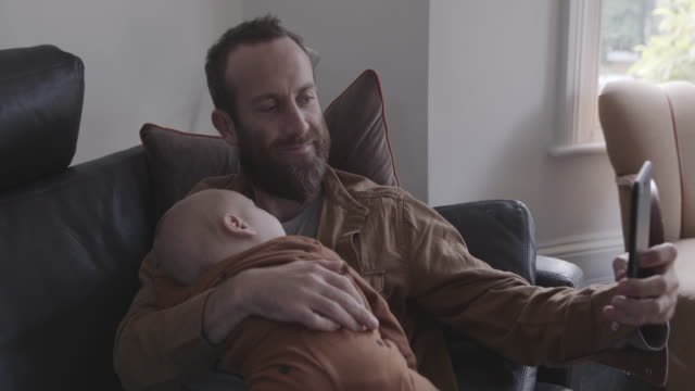 single father taking selfie with baby son on sofa - genderblend stock videos & royalty-free footage