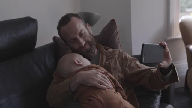vídeos y material grabado en eventos de stock de single father taking selfie with baby son on sofa - sms