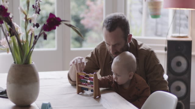 single father teaching his baby counting with abacus - single father stock-videos und b-roll-filmmaterial