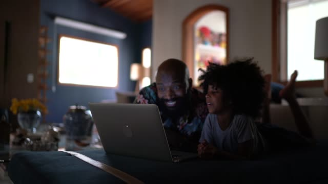 single father wacthing movie on a laptop with his daughter - single parent family stock videos & royalty-free footage