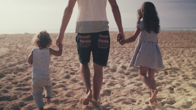 single father walking on beach with son and daughter, holding hands - familie stock-videos und b-roll-filmmaterial