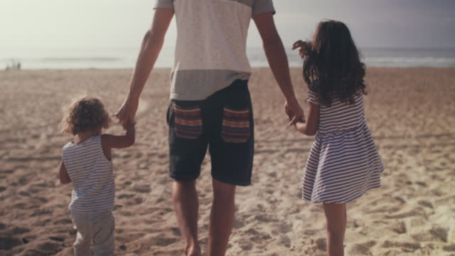 Single father walking on beach with son and daughter, holding hands