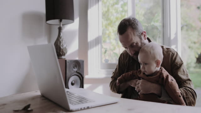 vídeos de stock, filmes e b-roll de single father working from home on laptop and looking after baby son - bebês meninos