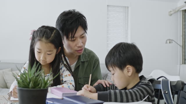 single japanese father helping his children with homework - single father stock-videos und b-roll-filmmaterial