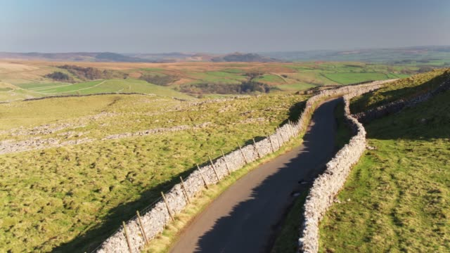 single lane road across yorkshire dales - drone shot - single track stock videos and b-roll footage