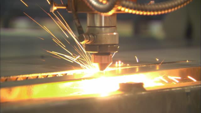vídeos de stock e filmes b-roll de cu ts single laser cutting device cuts through piece of steel during cutting process / livonia, michigan, usa - laser