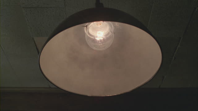 a single light lamp swinging from a ceiling turns on and off. - ランプ点の映像素材/bロール