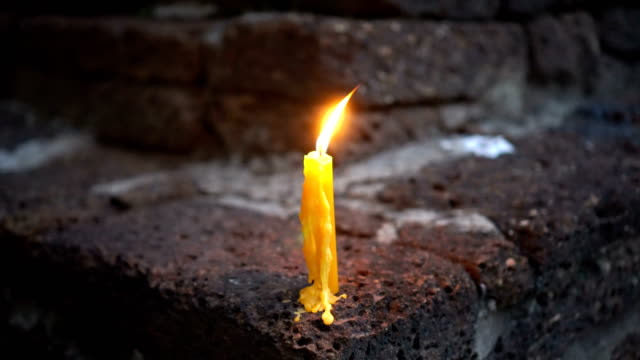 Single lit candle on the red brick