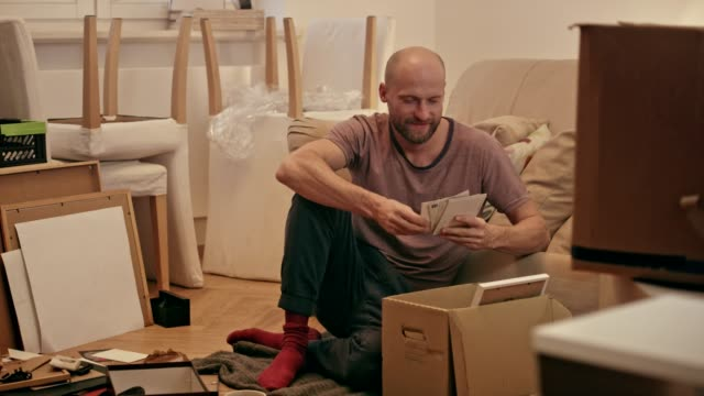 single man unpacking cardboard boxes in new apartment. - arranging stock videos & royalty-free footage