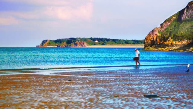vídeos de stock, filmes e b-roll de single man walking on tenby beach at low tide. - vazante