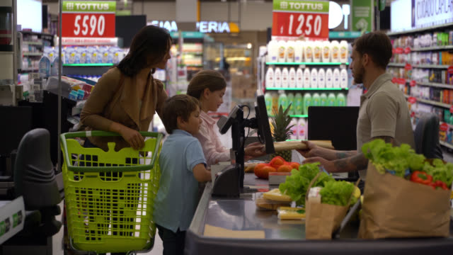 single mom and her two kids doing checkout at the supermarket handing groceries to male cashier - checkout stock videos & royalty-free footage