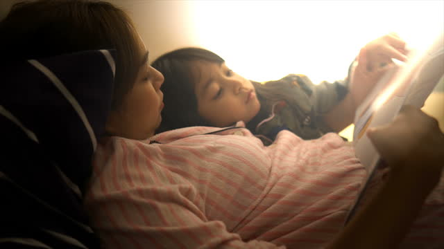 single mother reads stories to her daughter regularly before bedtime. - pyjamas stock videos & royalty-free footage