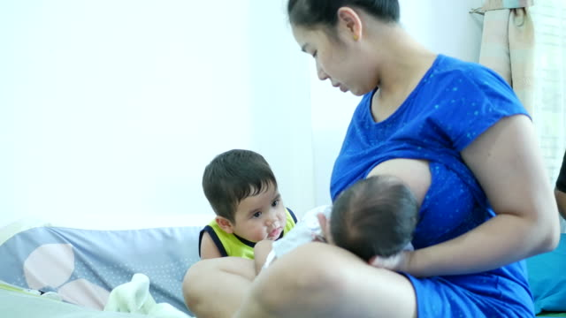 single mother take care her sons , one baby Breastfeeding