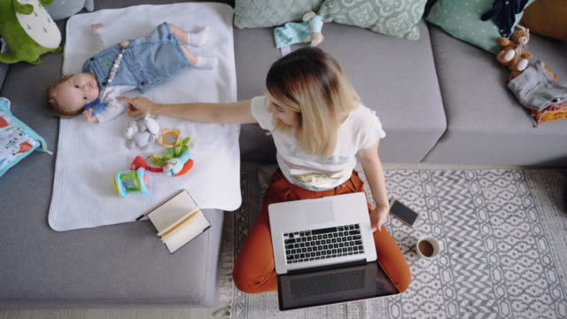 single mother working from home and playing with her baby boy - televisione a ultra alta definizione video stock e b–roll
