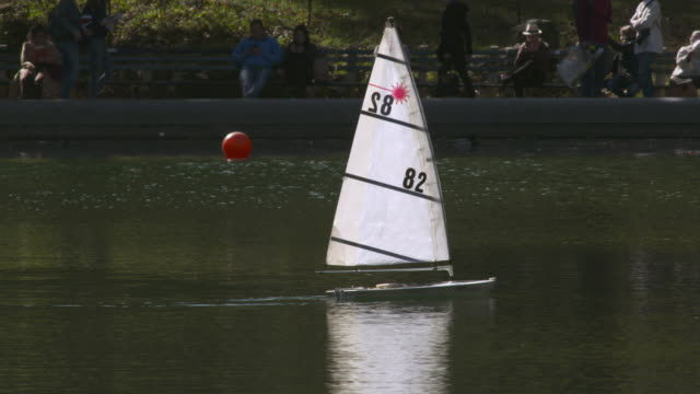 Single sail boat on pond in Central Park